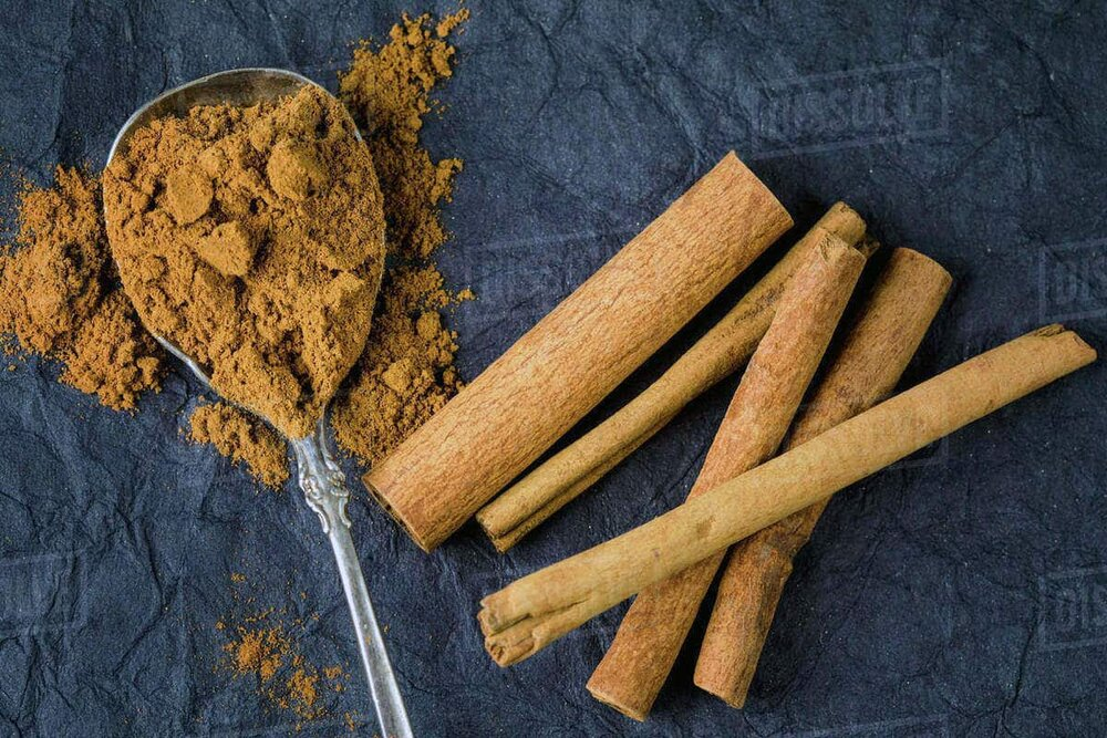 cinnamon sticks and cinnamon powder in a spoon