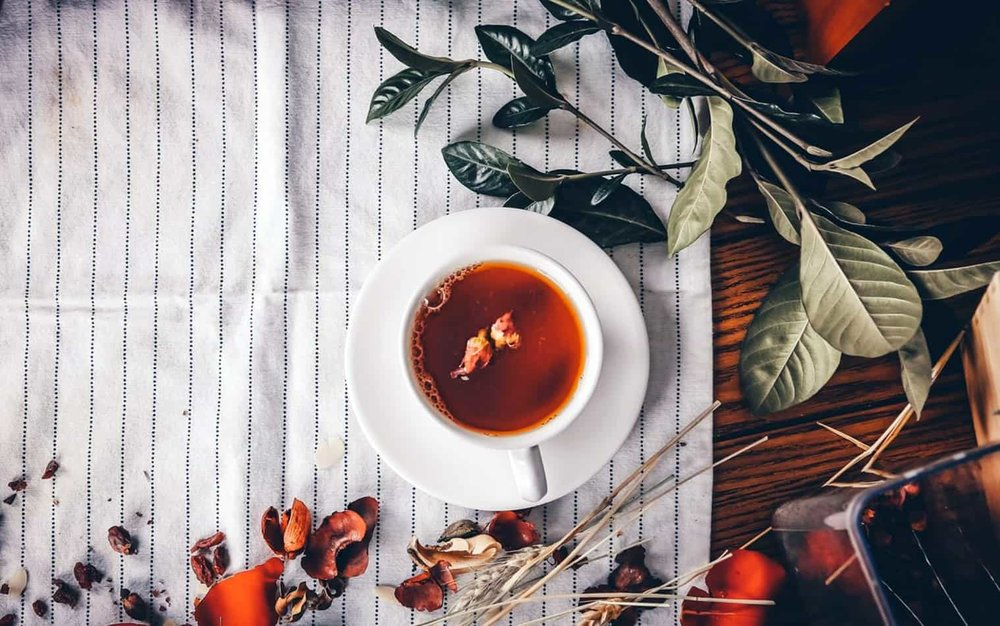 oolong tea cup on table cloth with leaves