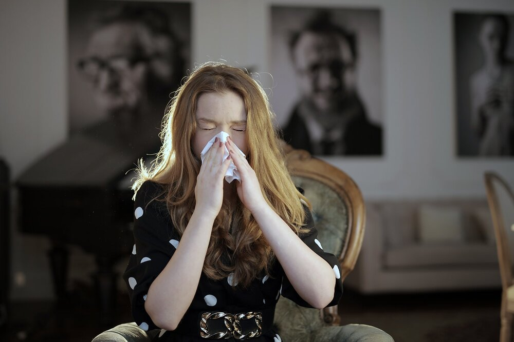 sick woman sitting on chair blowing her nose hay fever