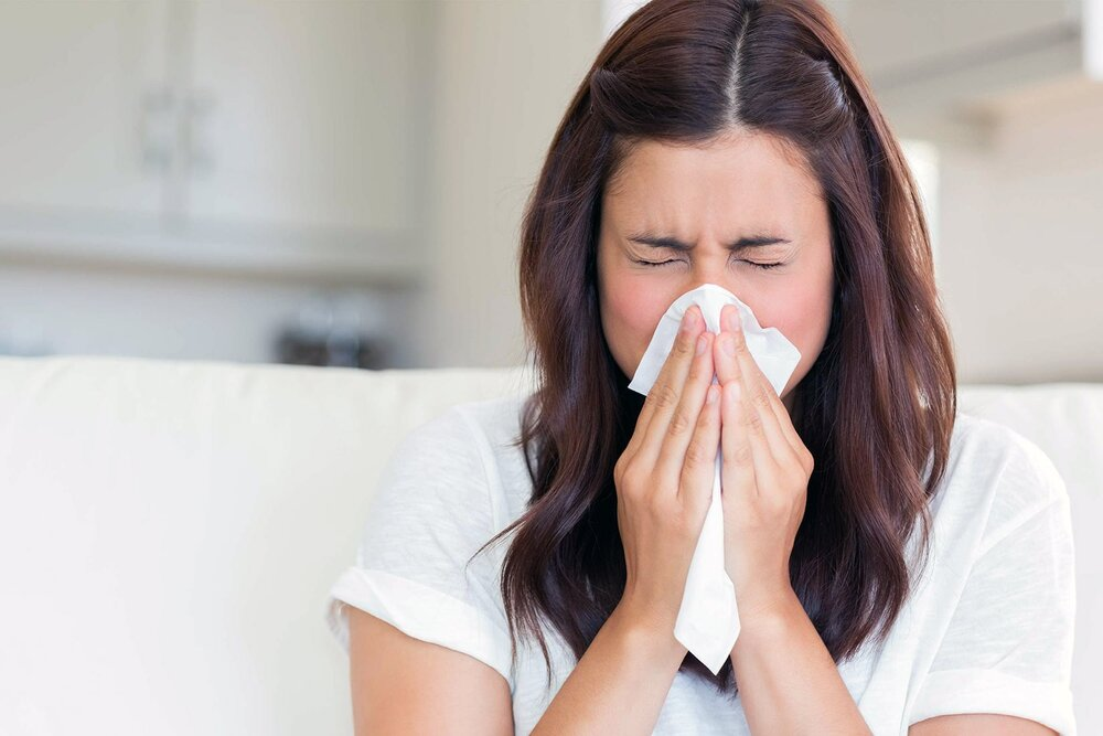sick woman sneezing blowing her nose hay fever