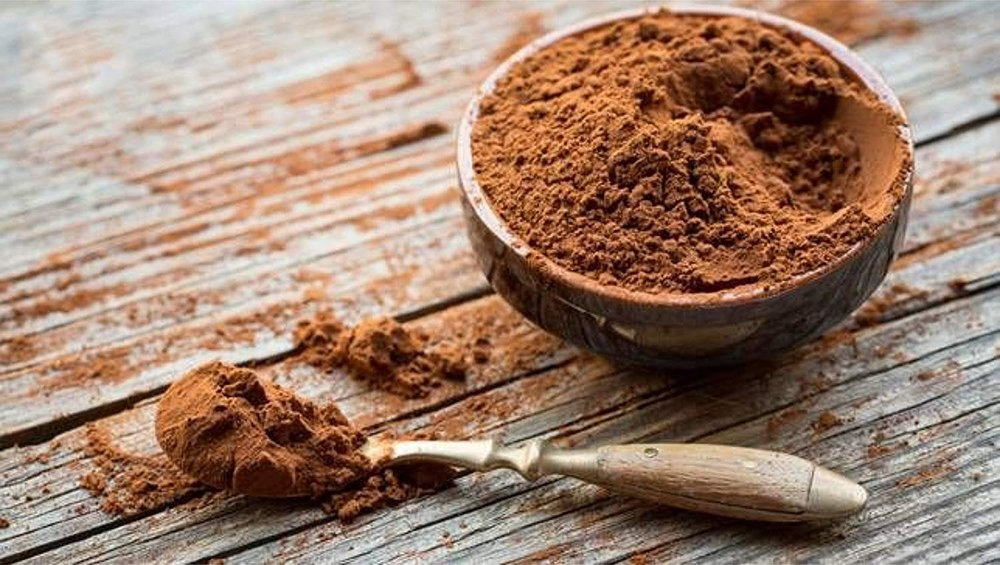spoon of cocoa powder on a table