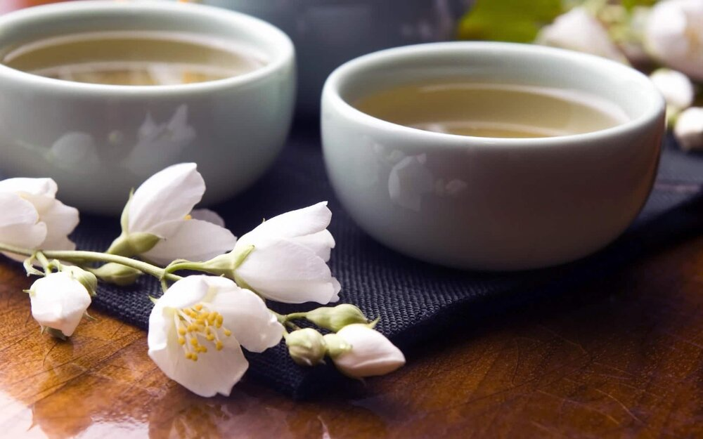 white tea cups and flowers on wooden table